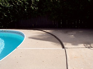 Before photo of sinking concrete pool deck