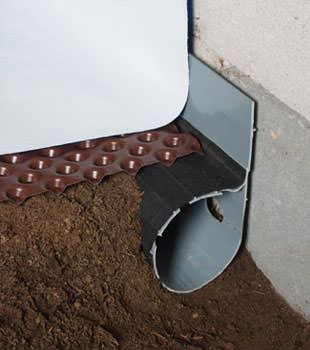 Closeup of a crawl space drainage system installed in Newport