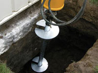 Installing a helical pier system in the earth around a foundation in Rutland